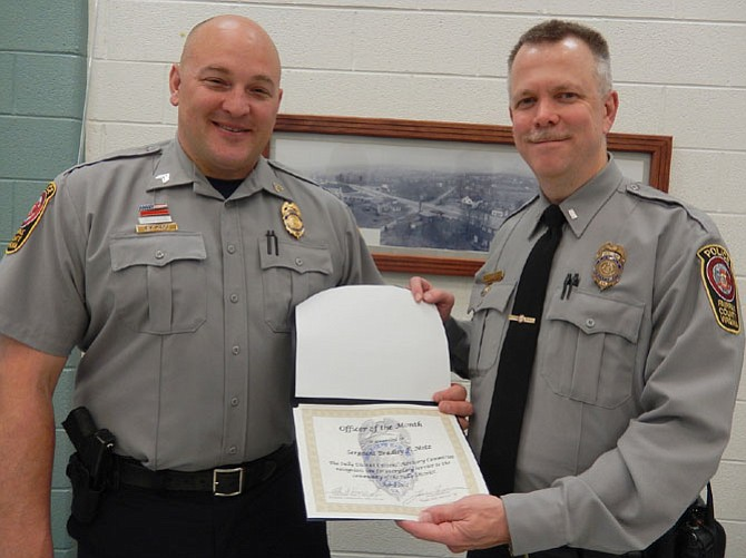 Police Sgt. Brad Metz (on left) receives his Officer of the Month certificate from the Sully District Station's assistant commander, Lt. Alan Hanson.