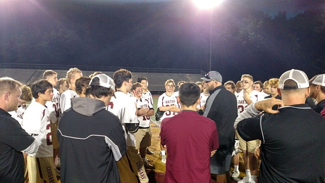 Oakton head coach Jake Bullock (center) addresses his team after losing in the state semifinal against South County on Wednesday, June 7.