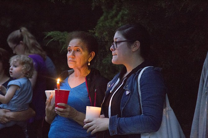 In an act of solidarity, Isabel Membreno of Sterling, left, and Laura Fuents of Sterling join a group of nearly 40 community members who showed up on Monday, June 19, to stand watch as Muslims enter the ADAMS Center mosque in Sterling for their evening Ramadan prayers.