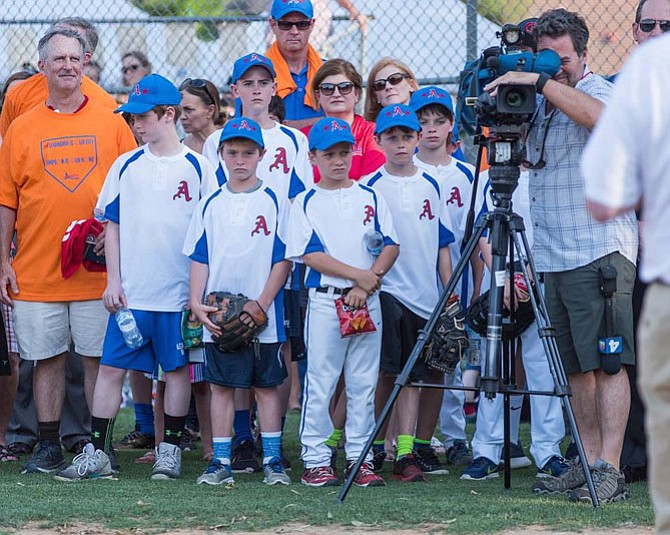 Alexandria Little League players listen to remarks prior to taking the field June 20 at Simpson Park.