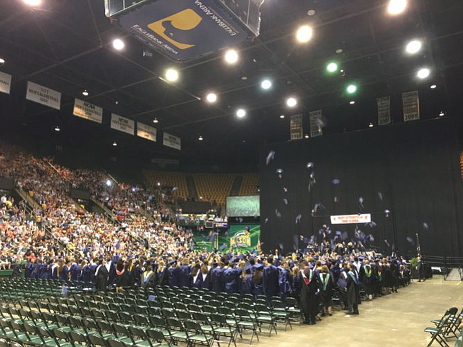 The now graduated Spartans throw their caps into the air.