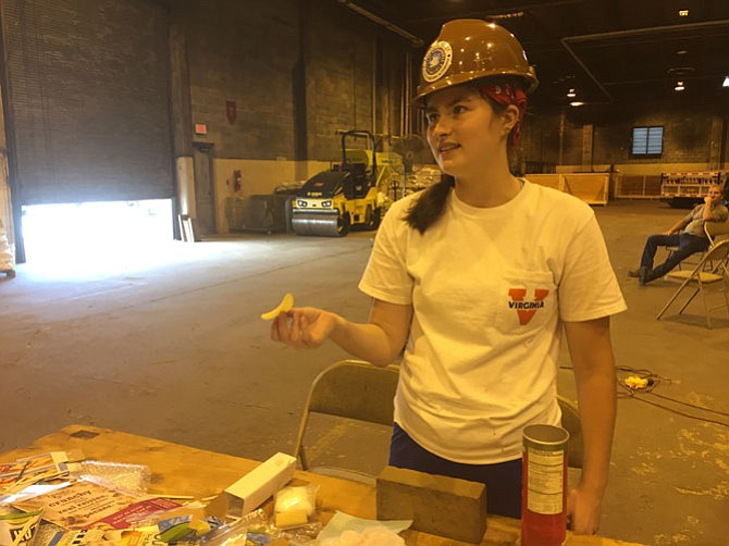 Addison Patrick, an intern with Alexandria Archeology, helps show visitors how difficult wrapping an artifact can be by having them wrap a Pringles chip to withstand the weight of a brick.