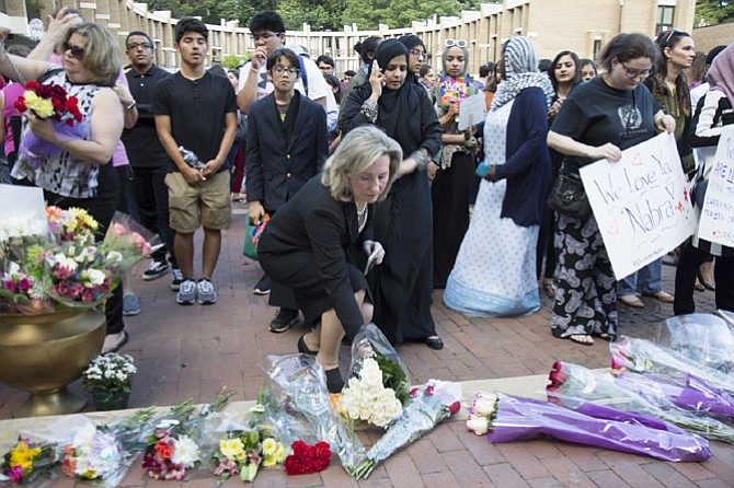 U.S. Rep. Barbara Comstock (R-10) placed a bouquet of white roses on the stage at Lake Anne Plaza during the vigil for Nabra before she gestured the sign of the cross.