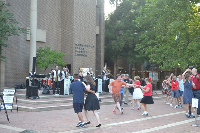Couples swing dance to music played by Radio King Orchestra.