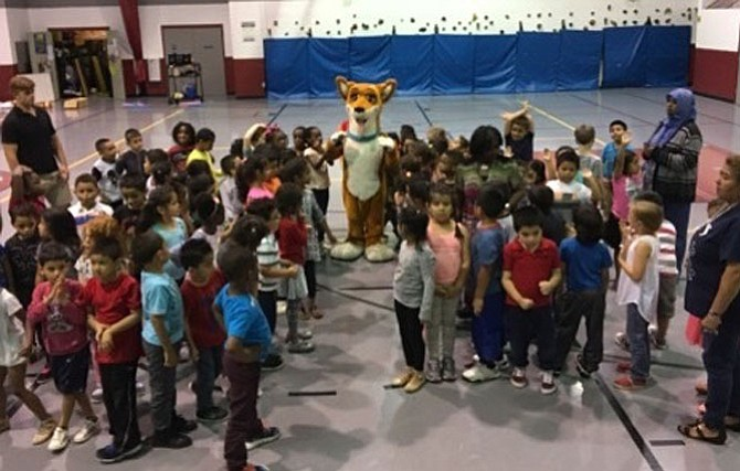 """Students from Cora Kelly School for Math, Science and Technology celebrate with Jazz the Dream Dog at the June 21 premiere of their original """"Lead – Don't Follow"""" music video. The video was written and produced by the students as part of the Kids Empowering Kids program."""