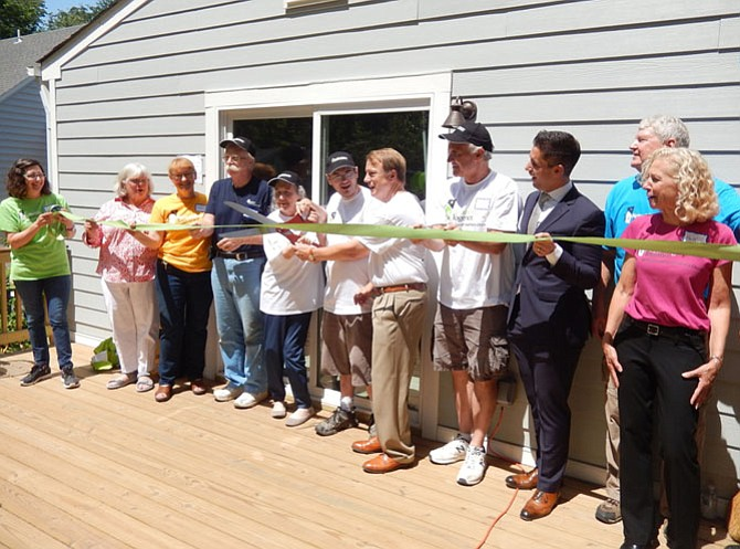 David Meyer cuts the ribbon on the Olivers' rebuilt home in Fairfax.