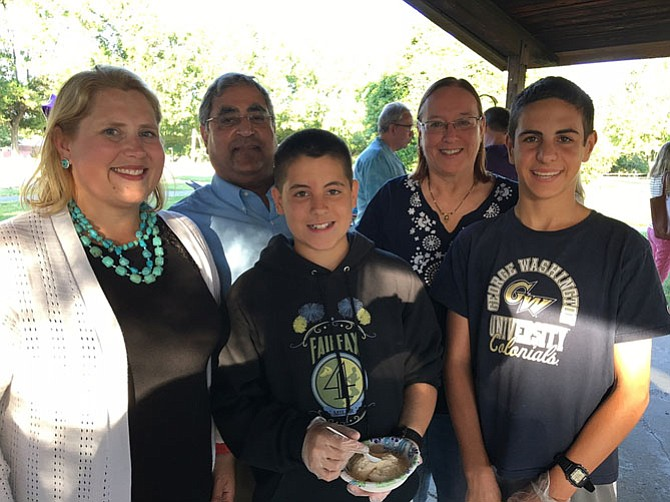 (Front row, from left) are Jennifer Passey and sons Liam, 12, and Eamon, 14; (back row) are her in-laws, Sahdev and Carolyn Passey, at the ice-cream social.