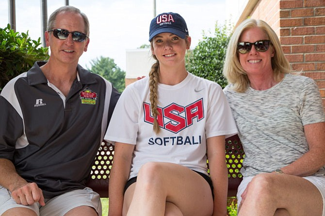Kathryn Sandercock, rising senior at Bishop O'Connell High School, poses for a picture outside of McLean High School with her parents Colin and Trish Sandercock. This summer she was in Oklahoma pitching for the US Junior Women's National Team.