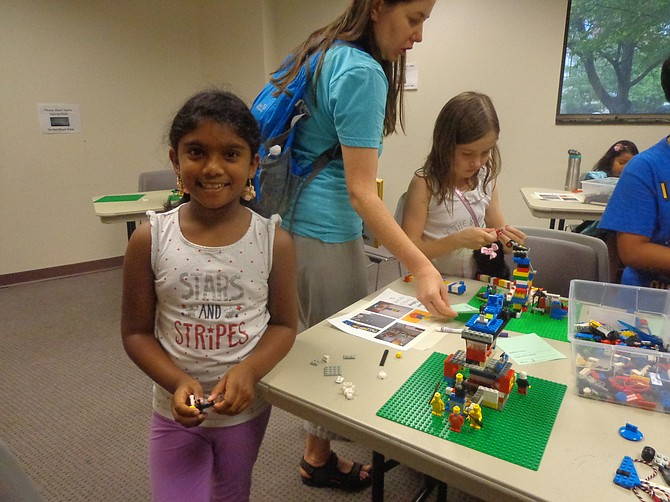 Seven-year-old Prisha Neelapala smiles for the camera while attending Lego Club, which gathered at Herndon Fortnightly Library on July 14.