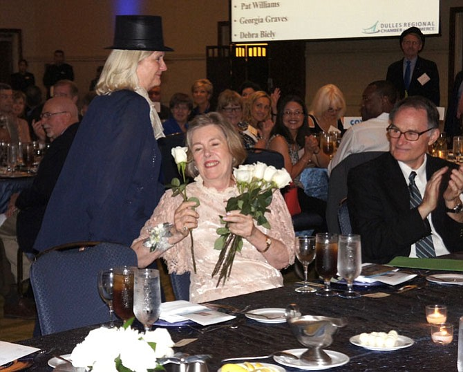 At her retirement celebration, Dulles Regional Chamber of Commerce President and CEO Eileen Curtis was honored with a parade of former Chamber Board Chairpersons, wearing top hats and each presenting the honoree with a rose.