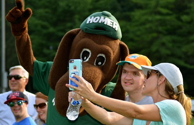 John Bogasky III (center) and Jillian Copeland (right) take a selfie with the Bethesda Big Train mascot, Homer, at Main Street's July 12 community-builder.