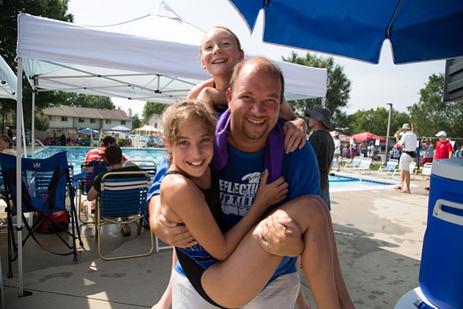 Dylan Evans, 38, works at Parks and Recreation of Loudoun County. He coaches the Reflection Riptides and is pictured here holding 11-year-old swimmers, sixth graders Grace Dowell and Caitlyn Allain.