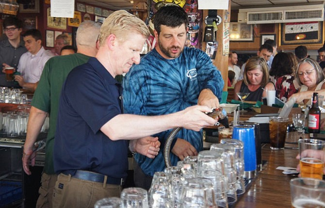 """That's how it's done: BridgeStreet CEO Sean Worker gets a few tips from real Jimmy's Old Town Tavern bartender Justin Fedorchak as Worker starts his """"shift"""" as a """"celebrity"""" bartender to help raise funds for nonprofit FISH."""