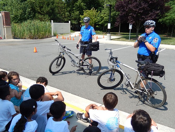From left: Bike team officers Eli Nunley and Matt Lasowitz tell children about the importance of wearing bike helmets and having bike locks.