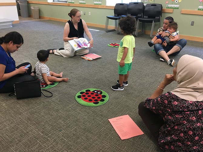 Youth Services Assistant Alexis Froyd reading to children during morning story time at the Dolley Madison Library in McLean.