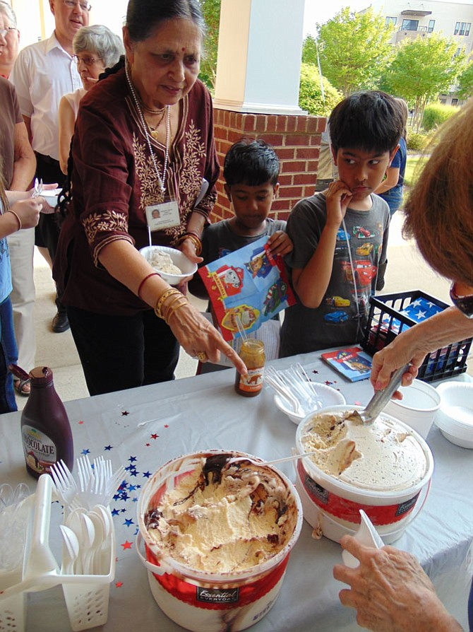Champa Kumar and her grandchildren Neel, 8, and Ved Prakash, 5, line up for ice cream during National Night Out at the Spring Hill Community, a 55-plus senior community in Lorton, on Tuesday, Aug. 1, 2017.