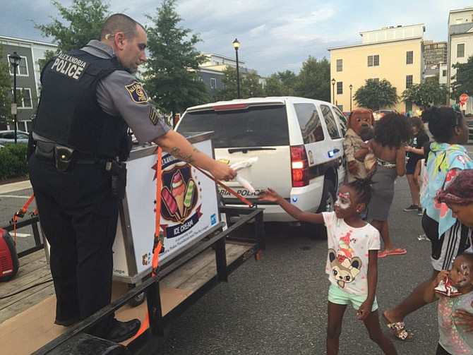 Officer Nick Ruggiero hands out ice cream near the the Charles Houston Recreation Center.