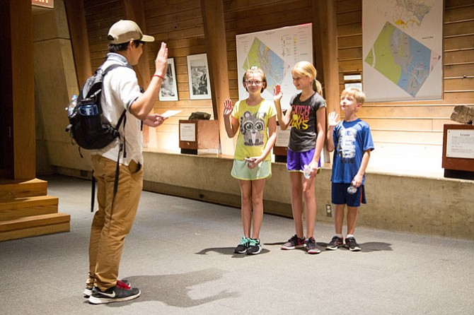 Ewan Clark, 18, a Youth Conservation Corps leader, swears in three junior members at the visitor center at Great Falls National Park on Thursday, Aug. 3.