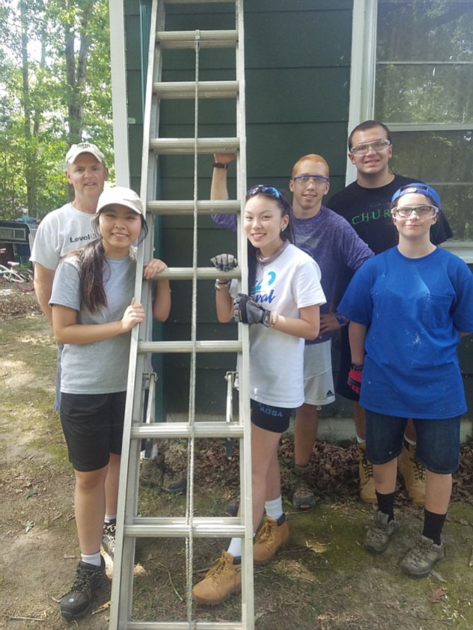Lily McIntire to right of ladder with crew members at the Diocese of Arlington's WorkCamp 2017.