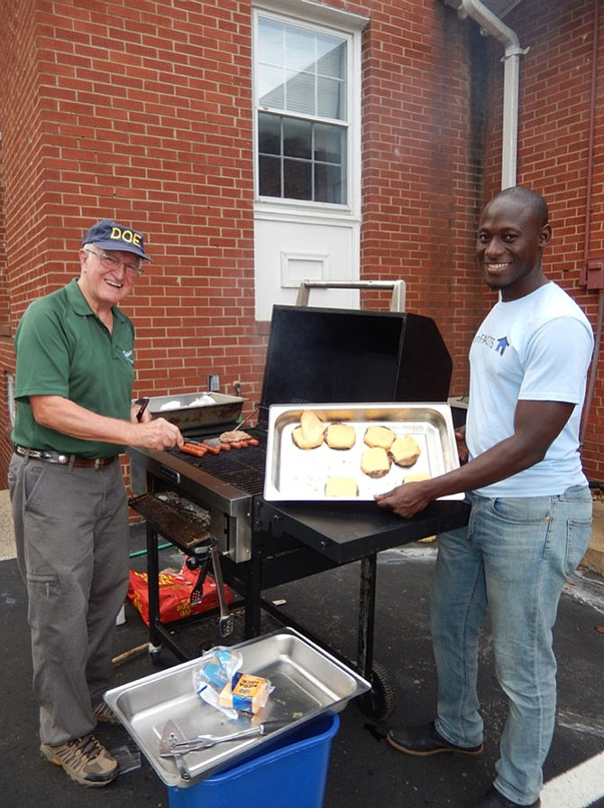 Henry Weigel (left) and Tijani Musa grill hot dogs and hamburgers for Ragan Oaks's National Night Out at Centerpointe Church in Fair Oaks.
