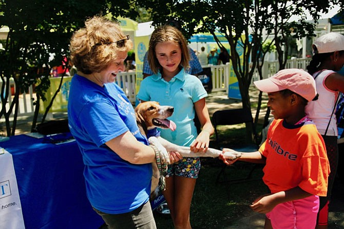 Volunteer Robin Turner brought her rescue dog with the unforgettable name of Journey. Lively, friendly, this American foxhound-mix enjoyed the crowd and shook hands with two admirers, Abby Gloekler, 11 of Annapolis and Anissa Jean-Claude, 8 who also played in the Family Day tennis clinic.