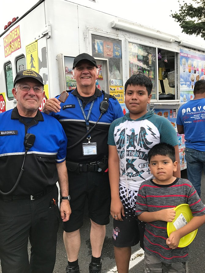 "Kevin Garcia, 12, of the Town of Herndon and his brother Fernando, 6, talk with Herndon Police Department Civil Volunteers Steve Marshall and Fred Kibler. Asked what they what they want to be when they grow up, Kevin quickly responds a lawyer, but Fernando quietly says, ""Quiero ser policia. Son mis amigos."""