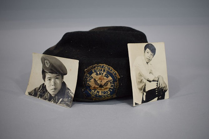 A hat and photos from a South Vietnamese soldier left behind at the Vietnam Memorial.