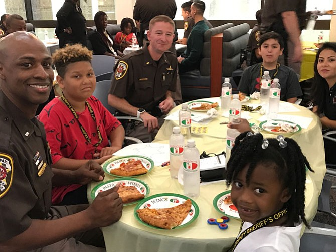 1st Lt. Jamal Perkins, Le Bron, 12, 2nd Lt. Shaun Timothy, Josh, 9, Katia Brizuela of Fairfax County Federal Credit Union, and Ja'Kayla, 5, enjoy a pizza party at the Fairfax County Courthouse Atrium Cafe.