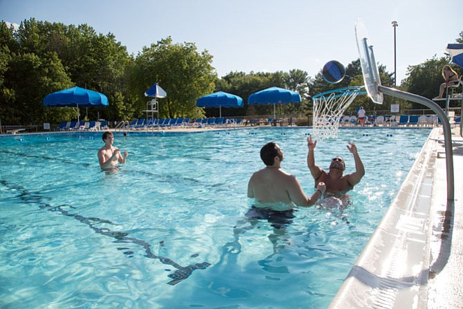 Chip Ponsart, 18, a freshman in college and a lifeguard at Greenbriar Pool Club; Ramone Nickens, 31, a Fairfax resident and Office Manager at ManTech International; and Logan Alderman, 18, a student and Fairfax resident play water basketball at Greenbriar Pool Club in Fairfax.