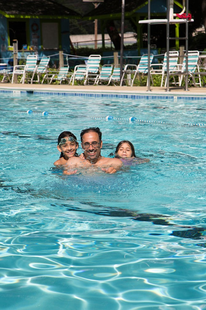From left: Springfield residents Adam Alsaegh, 9, rising fifth grader, his father Zuhair, 49, a teacher, and Zara, 8, a third grader pose for a picture at the North Springfield Swim Club pool in Springfield.
