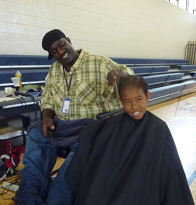 Del Ray barber Gary Bailey gives Tim Wiggins a haircut at a previous Community Kids Day. This year's back-to-school event will take place Wednesday, Aug. 23, at the Gum Springs Community Center.