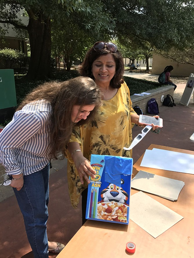 Vienna resident Ritu Kansal who teaches chemistry at NOVA's Annandale campus demonstrates the correct way to use a pinhole viewer.