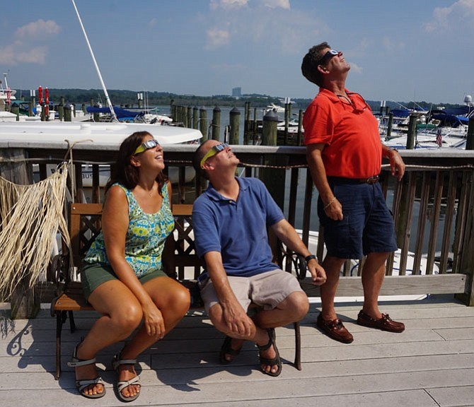 Elle and Richard Tauber join Jeff Carpenter in watching the solar eclipse Aug. 21 along the Alexandria waterfront.