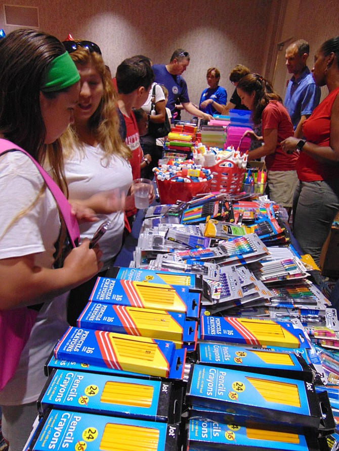 Children line up for school supplies at the Back-to-School Brigade, part of Operation Homefront at the Springfield Hilton Hotel on Saturday, Aug. 19.