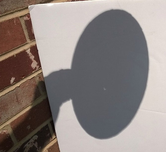 Partial solar eclipse seen at 2:22 p.m. Monday, Aug. 21 in the City of Fairfax through a crude pinhole viewer made by the photographer with a paper plate pierced by a nail and a screen fashioned from a foam presentation board.  The white crescent of sunlight not blocked by the shadow of the moon resembles the tip of a fingernail.