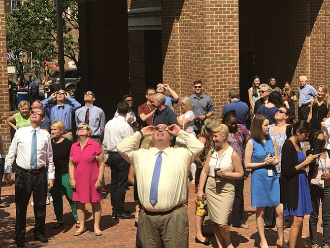 Members of the Old Town Alexandria legal community view the eclipse while standing in the courtyard outside the City of Alexandria Courthouse.