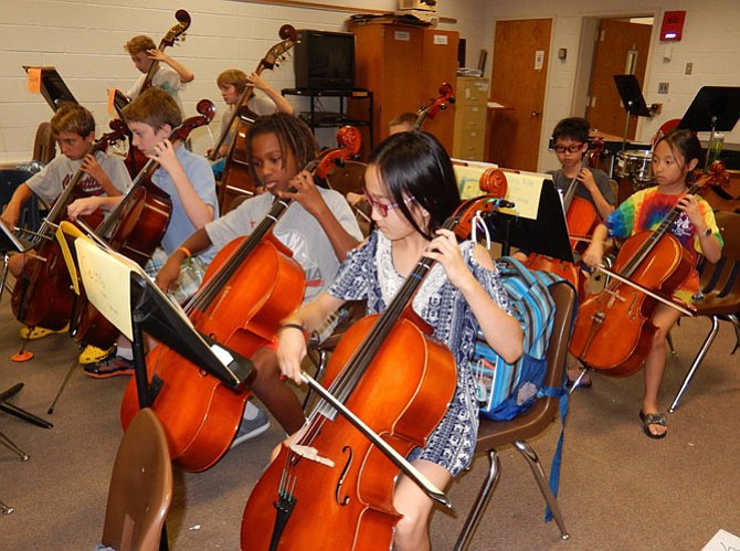 Cello players focus on their music during an intermediate-orchestra rehearsal.