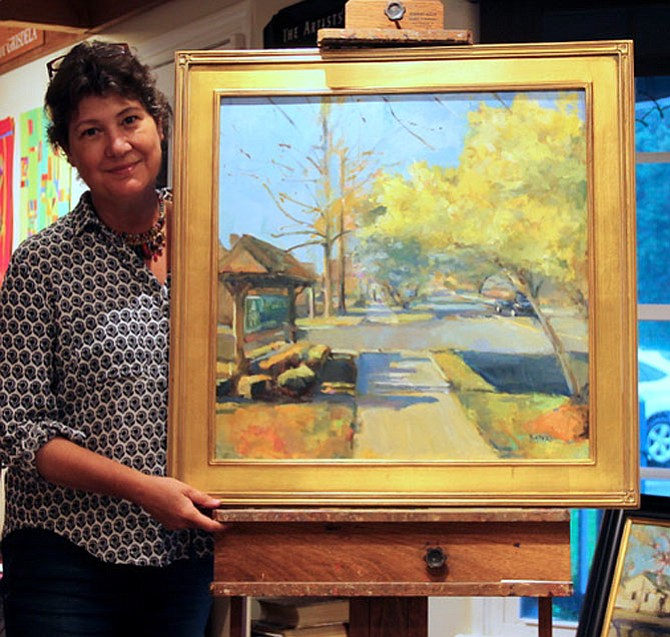 "Oil Painter Jill Banks holds her painting, ""Village Centre Walk,"" which depicts Walker Road as it may look when the 17 newly-planted trees reach maturity. The donated painting is being raffled off by the Celebrate Great Falls Foundation to support the Streetscape Project. Up to 100 raffle tickets at $50 will be sold and can be purchased by credit card or via PayPal online at www.celebrategreatfalls.org/great-falls-streetscape."
