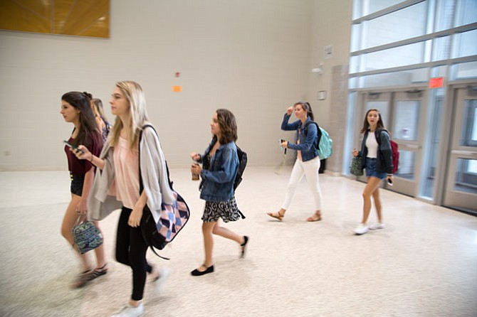 Students walk in the front doors for the first day of school for the 2017-2018 school year at Langley High School Monday morning.