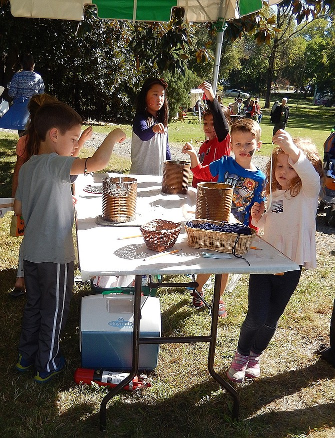 Children dip strings in wax to make candles during Centreville Day 2016. This year's event is Oct. 21.
