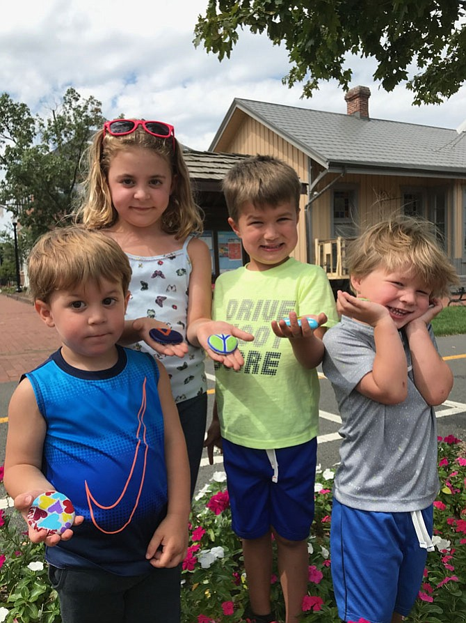 From left: After enjoying Farmers Market Fun Days produced by Parks and Recreation at the Herndon Town Square, Calvin Yetik almost 3, sister, Juliet, 6, and friends Connor Witaker 4, and his brother, Blake, 2, all of Reston, show off their painted rocks they are about to hide near the Herndon Depot Museum.