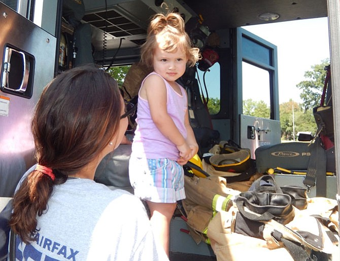 Stella Kesner, 2, explores a fire engine while Firefighter/Paramedic Kathryn Schmidt looks on.