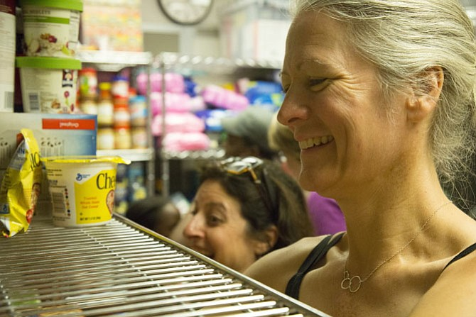 South Lakes High School Parent-Teacher-Student Association Member Amy Shaw organizes food at the pantry in July.
