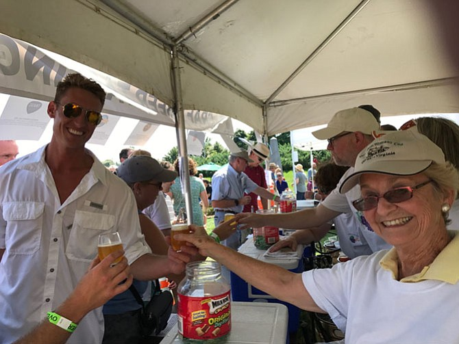Charles H. Harbaugh, IV, Mayor of Middletown receives his craft beer sample from Gerri Ludwig, Herndon Woman's Club, at the Labor Day Festival.