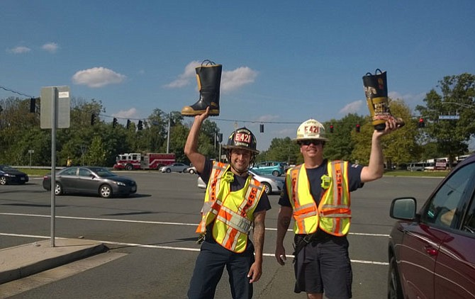 Fairfax County Fire and Rescue Master Technician Johnathan Macquilliam and Capt. Matthew C. Burns hold their boots high as they work a Labor Day crowd of generous motorists at a Fairfax traffic signal on Waples Mill Road and U.S. Route 50. They helped their Station 21 in Fair Oaks raise $14,200.12 in just four days, Sept. 1-4, for MDA Greater Washington, D.C., and the International Association of Firefighters disaster relief fund.