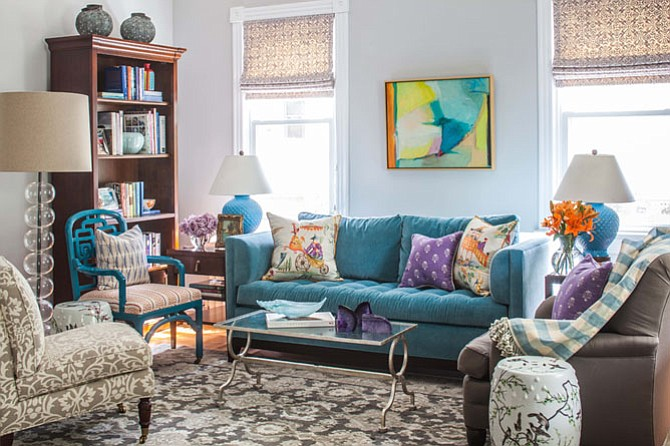 In this room by Susan Nelson of Home on Cameron, the soft gray and lavender tones provide a backdrop for the brightly colored sofa and accessories.