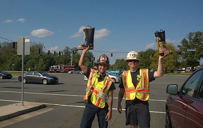Fairfax County Fire and Rescue Master Technician Johnathan Macquilliam and Capt. Matthew C. Burns hold their boots high as they work a Labor Day crowd of generous motorists at a Fairfax traffic signal on Waples Mill Road and U.S. Route 50.