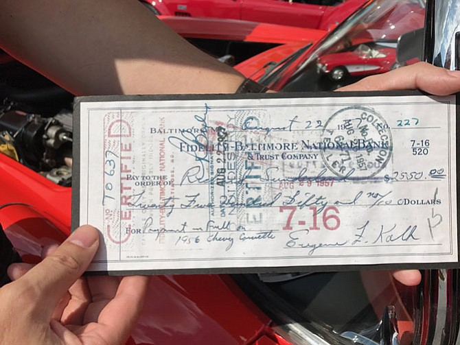 "John Kolb holds a copy of the original canceled check his father wrote for $2,550 to pay in full and purchase the red 1956 Chevy Corvette he now owns. ""$2,500 was a lot of money for an enlisted man at that time,"" Kolb said."