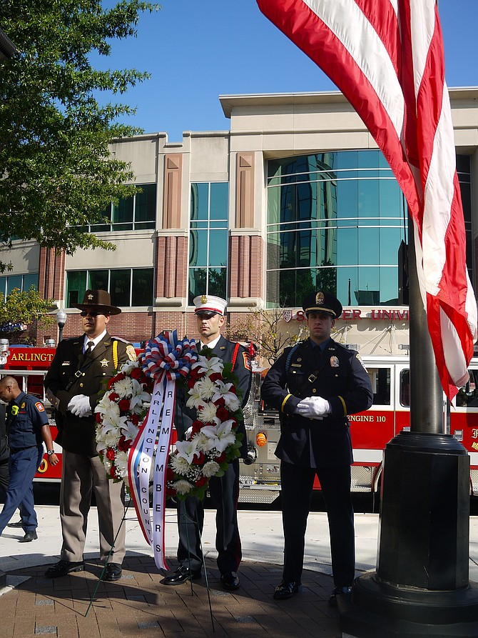 Lieutenant Laureano, Officer Vincent Ruggero of the ACPD, and Captain Ben O'Bryant, of the ACPD, stand behind the wreath. More than 100 Arlington residents, and many of the county's emergency personnel and officials, came together at Courthouse Plaza on this Sept. 11 to remember the attack of 16 years ago.