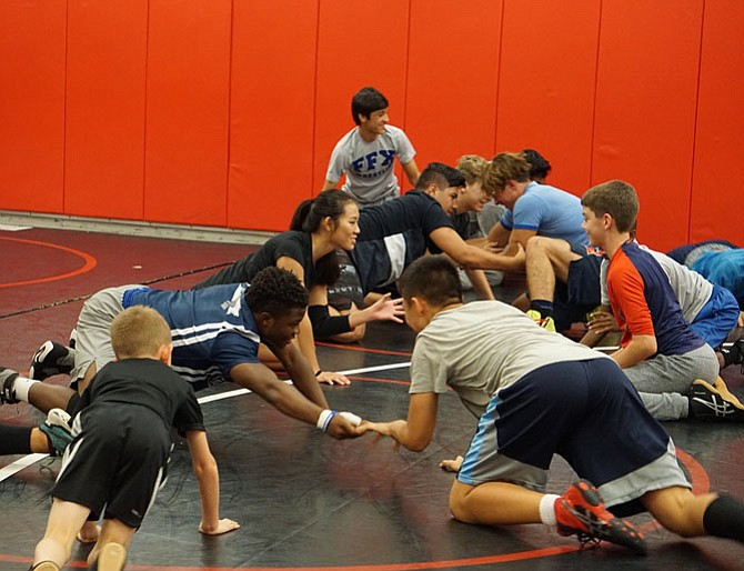 During their warmup time, NOVA wrestlers play a game to develop wrestling-specific skills.